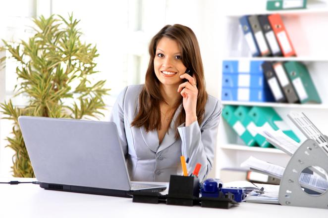 девушка секретарь разговаривает по телефону в офисе